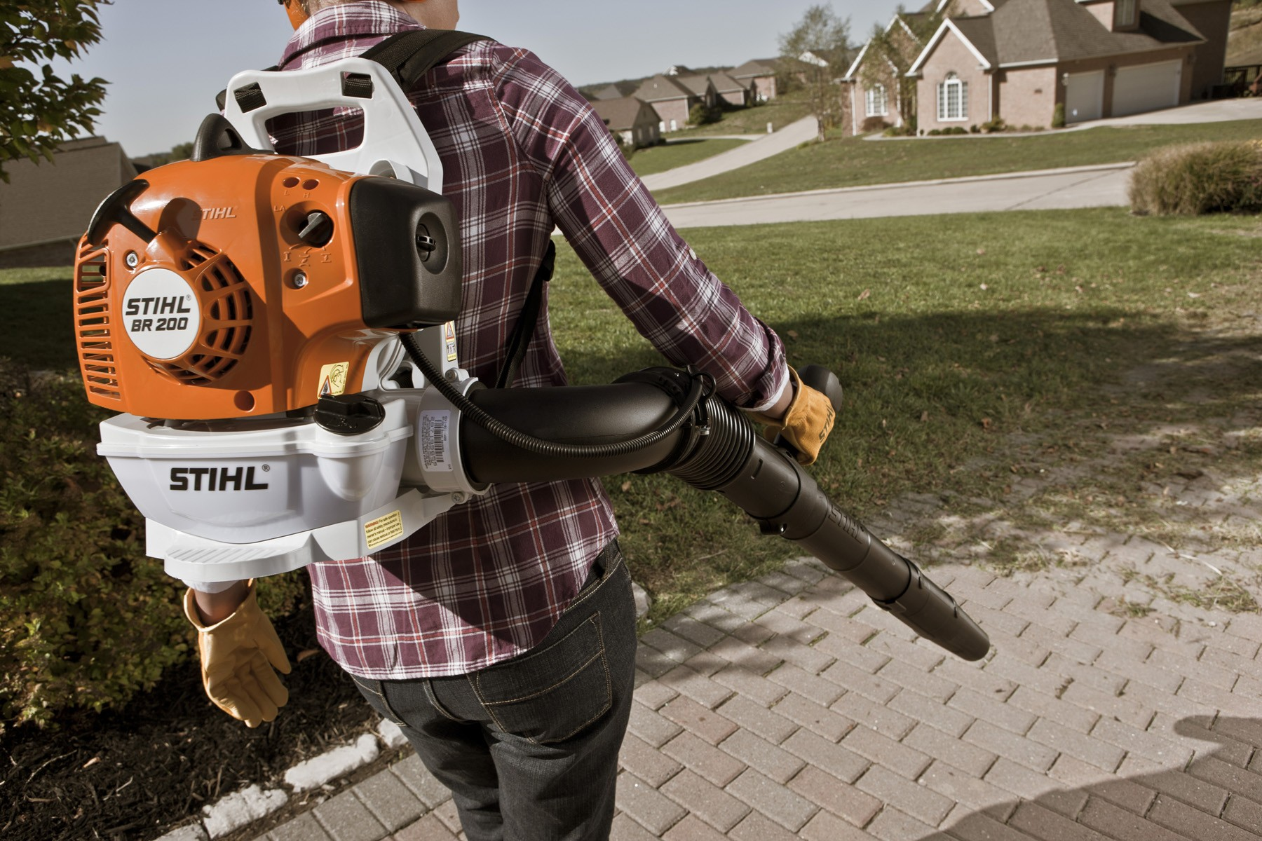 A backpack blower is being used for leaf removal.